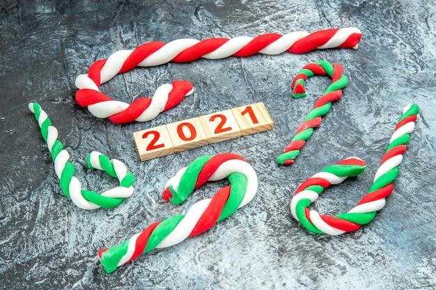 Bloco de madeira de doces de natal coloridos de frente na foto de ano novo com fundo cinza