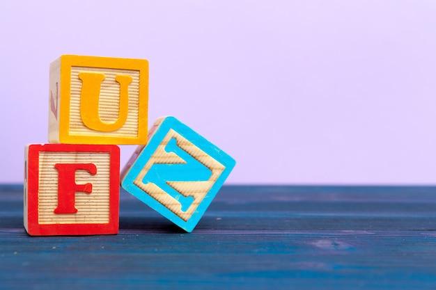 Bloco de madeira do cubo com alfabeto, construindo a palavra diversão