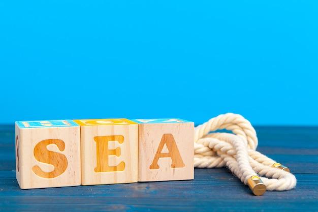 Bloco de madeira do cubo com alfabeto, construindo a palavra mar