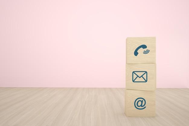 Bloco de madeira do cubo três que empilha com contato ícone que arranja em seguido no fundo de madeira. conceito de estratégia de negócios e plano de ação.