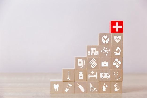Bloco de madeira do seguro de saúde que empilha com cuidados médicos do ícone médicos.