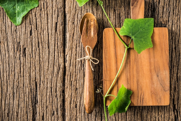 Bloco de madeira e colher e garfo no fundo de madeira