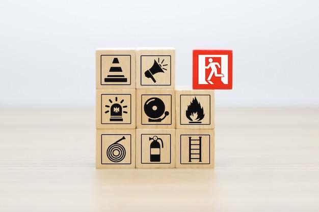 Bloco de madeira empilhando com ícones do fogo e da segurança.