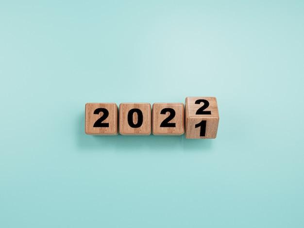 Bloco de madeira lançando de 2021 a 2022 sobre fundo azul para preparação de feliz natal e feliz ano novo, renderização em 3d.