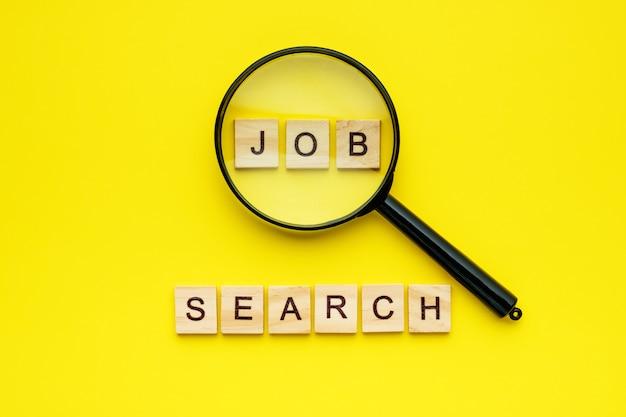 Bloco de madeira letras procura de emprego e lupa sobre fundo amarelo.