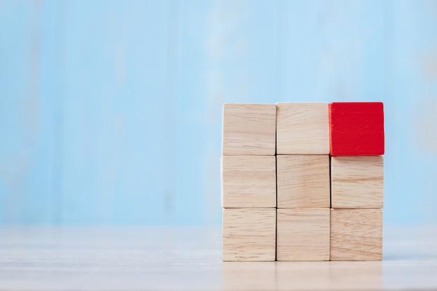 Bloco de madeira vermelho no edifício. planejamento de negócios, gerenciamento de riscos, solução, estratégia, diferente e única