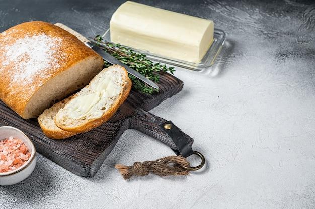 Bloco de manteiga e torradas de pão fatiadas em uma tábua de madeira com ervas