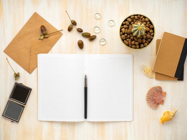Bloco de notas aberto branco, envelope kraft e cactus em pote deitado na mesa de madeira bege