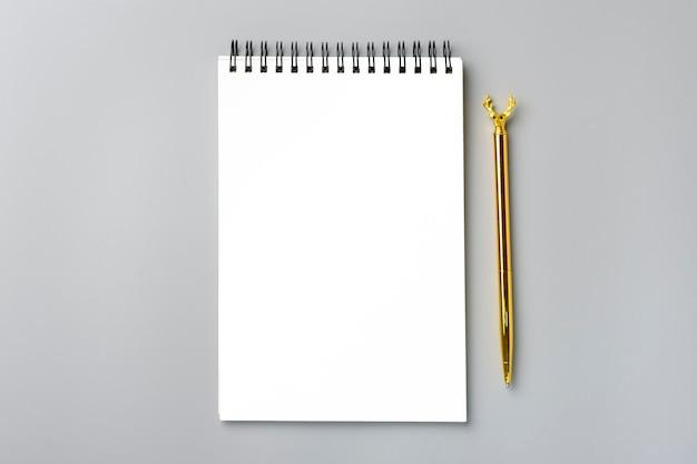 Bloco de notas aberto, caneta dourada plana