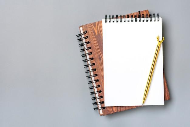 Bloco de notas aberto com caneta dourada isolada