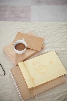Bloco de notas aberto com manchas de café, livros, planejadores e xícara com cappuccino na cama