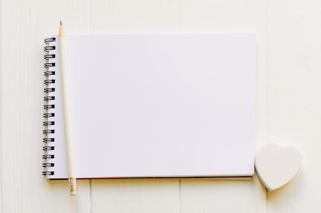 Bloco de notas aberto com página vazia para espaço de cópia com um lápis e coração de madeira branco