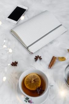 Bloco de notas aberto com smartphone perto de xícara de chá