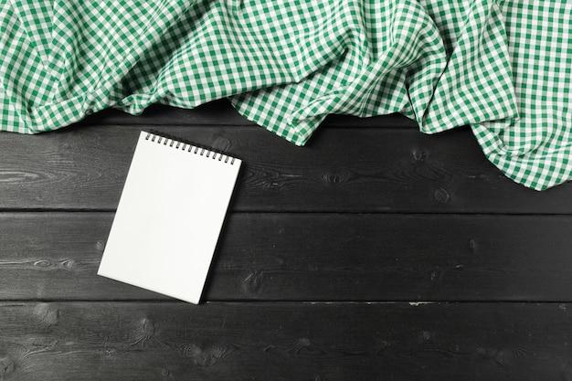 Bloco de notas aberto em branco sobre fundo de madeira com um pedaço de pano
