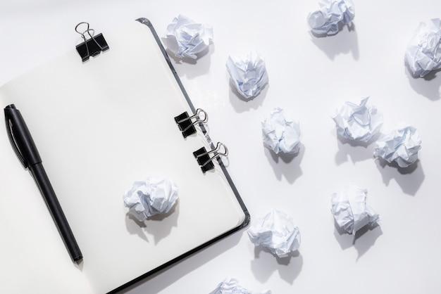 Bloco de notas aberto em um fundo branco com papéis amassados