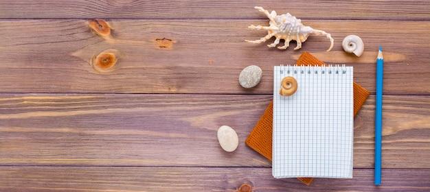 Bloco de notas aberto limpo para escrever, lápis, passaporte e concha do mar em madeira