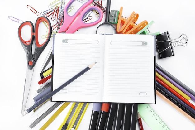 Bloco de notas aberto sobre material de escritório na parede branca.