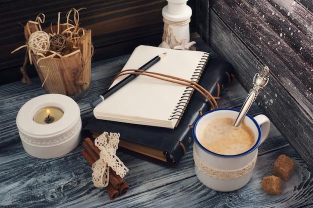 Bloco de notas aberto, vela, lápis e café