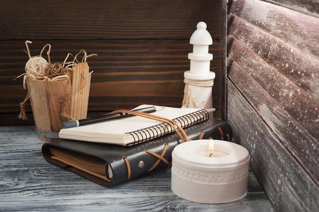 Bloco de notas aberto, vela, lápis e decoração