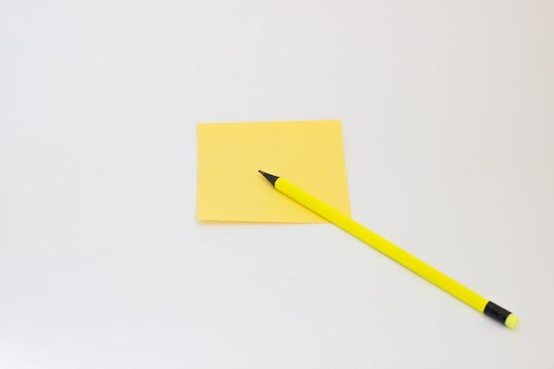 Bloco de notas amarelo e lápis amarelo sobre um fundo branco
