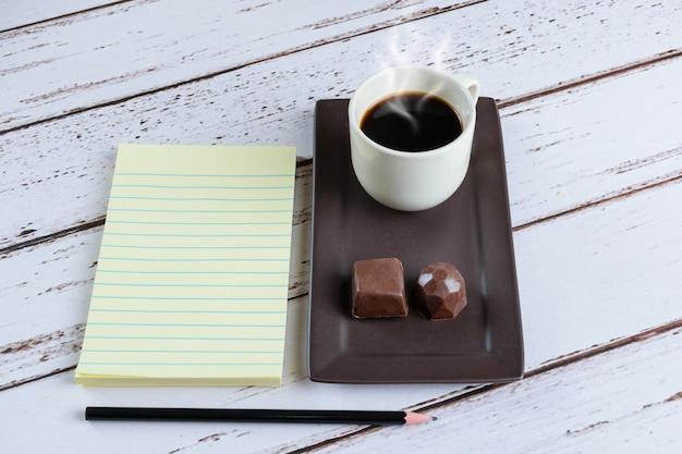 Bloco de notas ao lado de uma xícara de café e bombons de chocolate amargo.
