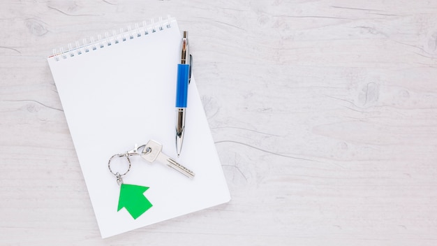 Bloco de notas arrumado com caneta e chave