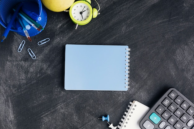 Bloco de notas azul fechado cercado com papelaria na lousa