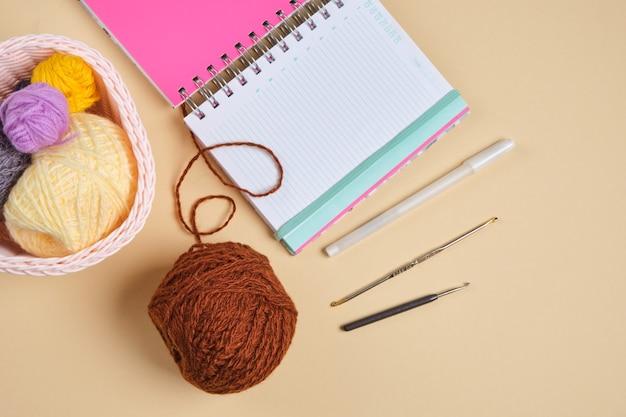 Bloco de notas, bolas de linha em uma cesta e ganchos de crochê em fundo bege