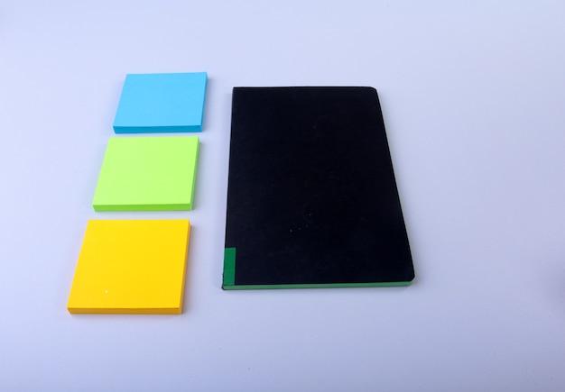 Bloco de notas branco com lembretes coloridos.