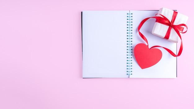 Bloco de notas branco em branco aberto, caixa de presente com fita vermelha e formato de coração de papel rosa em fundo rosa