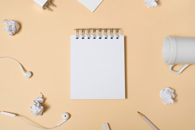 Bloco de notas branco em branco cercado por copo vazio; papel amassado; lápis; fone de ouvido sobre o pano de fundo bege