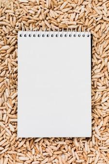 Bloco de notas branco espiral em branco sobre o arroz tufado marrom