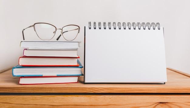 Bloco de notas branco, livros e óculos no local de trabalho