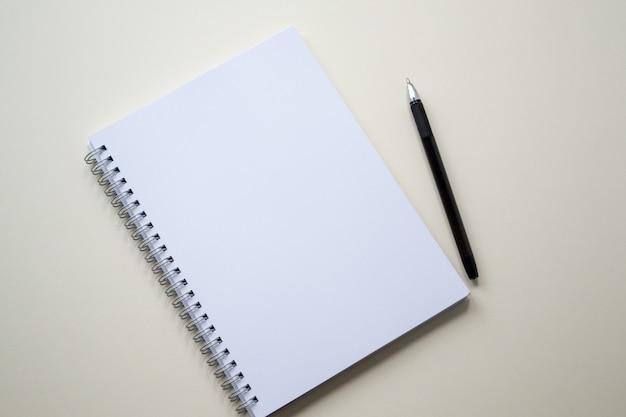 Bloco de notas branco vazio com caneta preta.