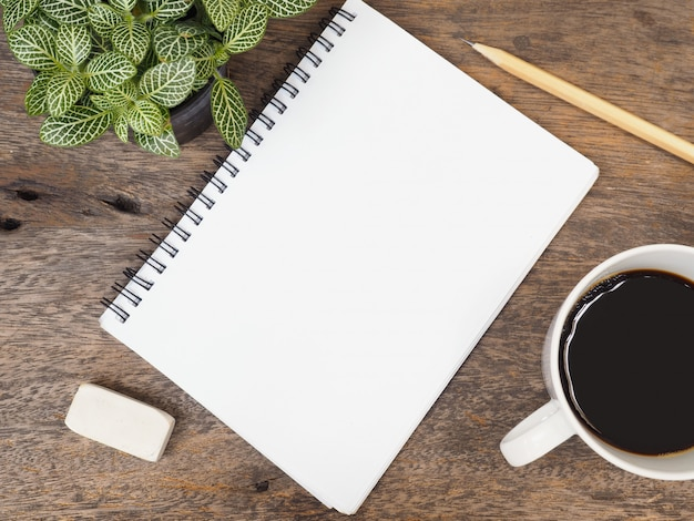 Bloco de notas, café e planta verde