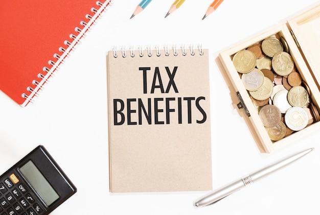 Bloco de notas calculado com caneta prata de três cores e caderno marrom com texto benefícios fiscais