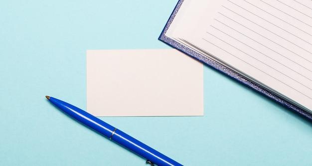 Bloco de notas, caneta branca e cartão em branco para inserção de texto ou ilustrações em parede azul claro. vista superior com espaço de cópia