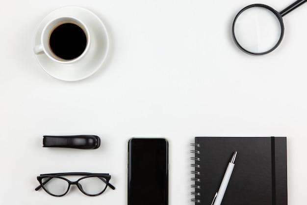 Bloco de notas, caneta, café, telefone inteligente, lupa, óculos no fundo branco, cópia espaço, configuração plana.