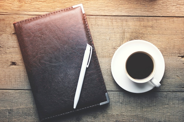 Bloco de notas, caneta e xícara de café preto na mesa de madeira