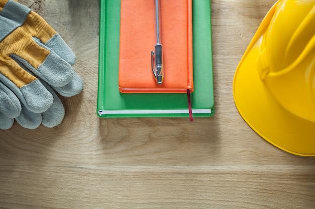 Bloco de notas caneta esferográfica luvas de segurança capacete na placa de madeira