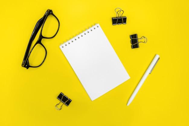 Bloco de notas, caneta, óculos e clipes de pasta em fundo amarelo. camada plana, vista superior, espaço de cópia.