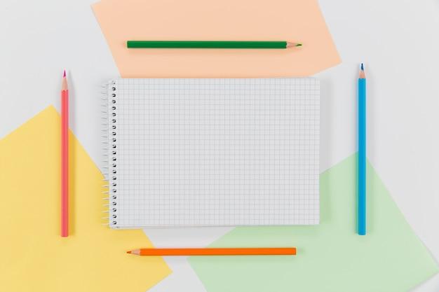 Bloco de notas cercado por lápis coloridos