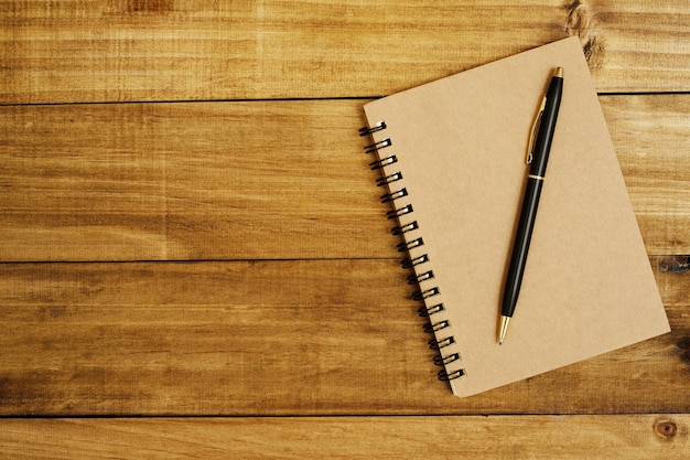 Bloco de notas colocado em um piso de madeira marrom e uma caneta