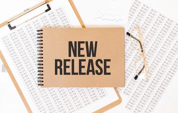 Bloco de notas colorido artesanal com o texto novo lançamento. bloco de notas com óculos e documentos de texto. conceito de negócios