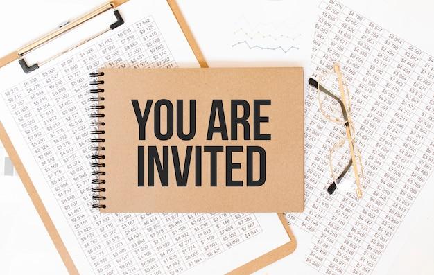 Bloco de notas colorido artesanal com o texto você está convidado. bloco de notas com óculos e documentos de texto