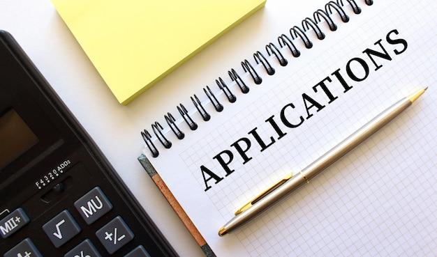 Bloco de notas com aplicações de texto, ao lado encontra-se uma calculadora e papéis amarelos. conceito de negócios.