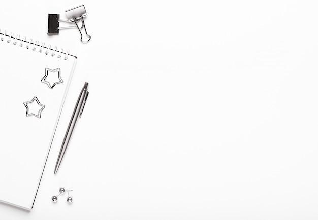 Bloco de notas com artigos de papelaria de prata, clipes de papel, botões e caneta em um fundo branco.