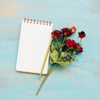 Bloco de notas com buquê de rosas.