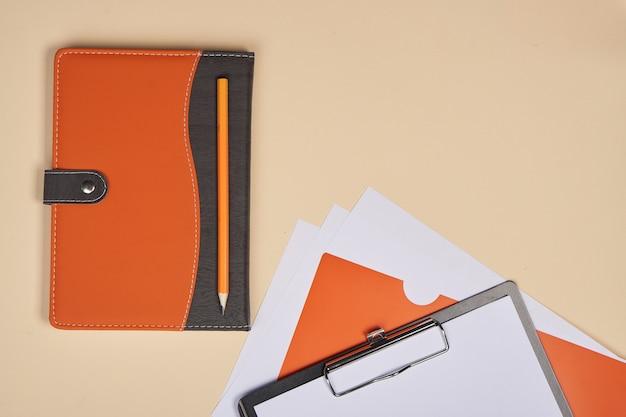 Bloco de notas com caneta acessórios de papelaria fundo bege pasta com lençol branco