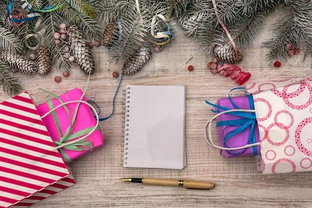 Bloco de notas com caneta e caixas de presente coloridas na mesa de madeira. comemoração e presentes